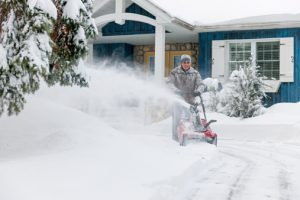 man removing snow to prevent hardscaping damage